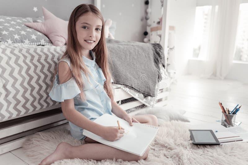 Menina alegre que senta-se no assoalho e na tiragem fotos de stock