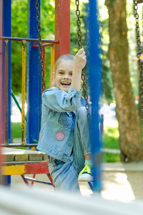 A menina alegremente e ri ferventemente o assento em uma escada de suspensão no campo de jogos foto de stock