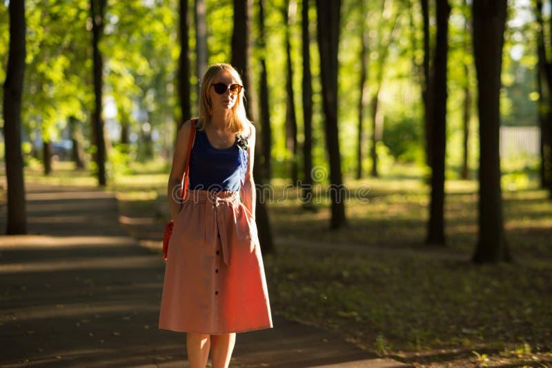 A menina alta magro com os óculos de sol vestindo do cabelo louro em uma parte superior azul e em uma saia leve anda no parque Cl imagens de stock