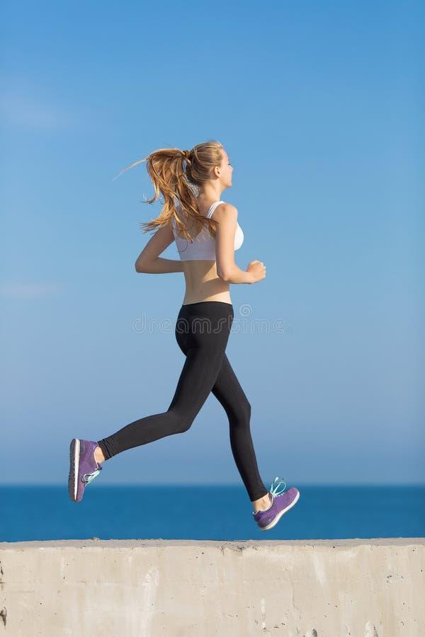 Menina alta magro que corre ao longo da praia fotografia de stock