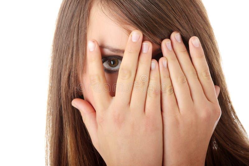 Menina amedrontada que esconde sua face fotografia de stock
