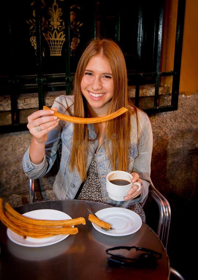 Menina americana do turista do estudante que senta-se comendo o chocolate quente típico do espanhol com o sorriso dos churros fel foto de stock