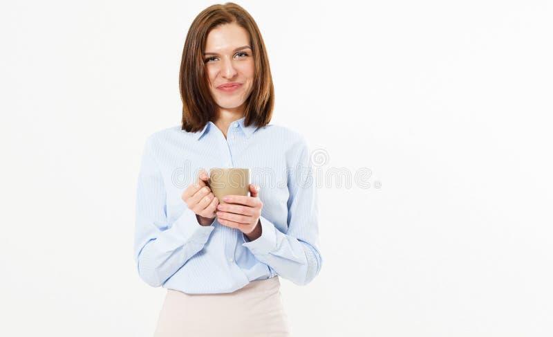Menina amigável bonita nova que guarda uma caneca de chá ou de café quente e que levanta em um fundo branco imagem de stock