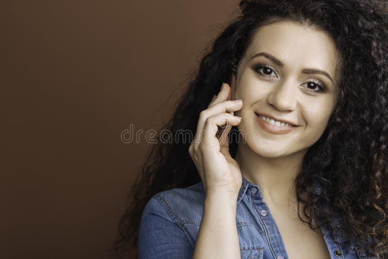 Menina amigável que guarda o telefone perto da orelha imagem de stock