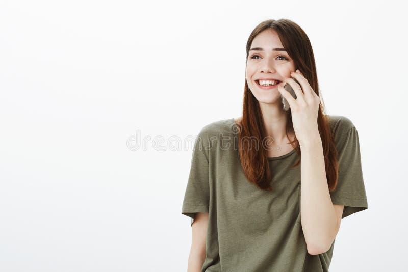 A menina amigável tagarela gosta de falar no telefone celular Retrato da mulher despreocupada feliz no equipamento ocasional, sor fotos de stock royalty free