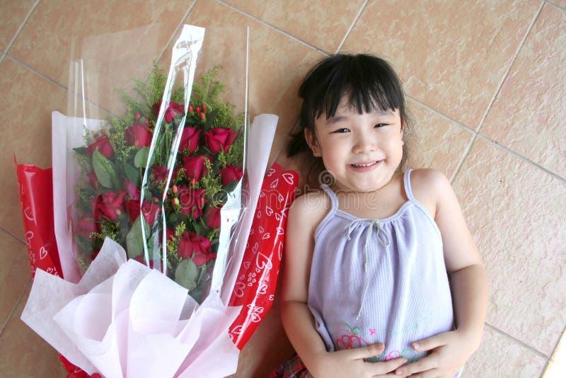 Menina & ramalhete das rosas que encontram-se no assoalho imagem de stock royalty free