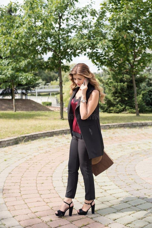 a menina anda através do parque com um saco de compras e os telefones foto de stock royalty free