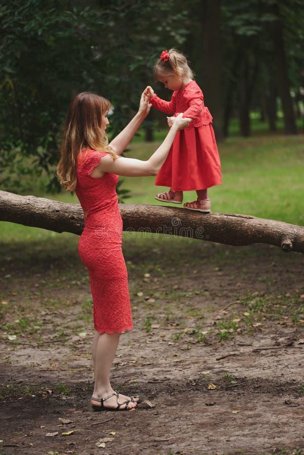 A menina anda na árvore com mamã imagem de stock