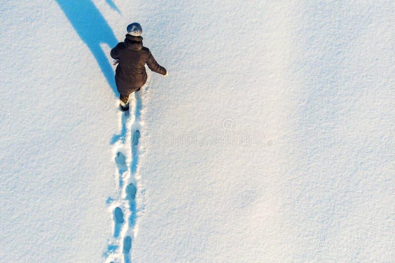 A menina anda ou vai na neve que sae de pegadas, vista aérea superior Fundo da atividade exterior do inverno com espaço da cópia fotografia de stock