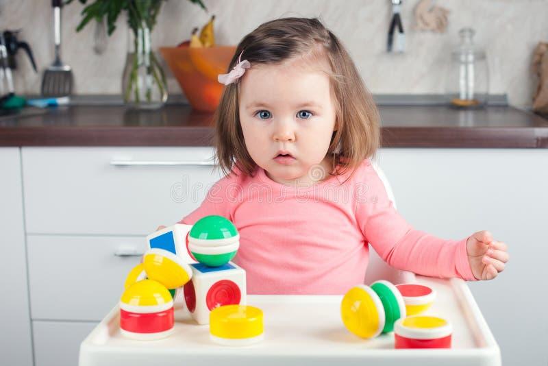 Menina 2 anos velha com o cabelo longo que joga com constru??o do desenhista em casa, em casa antes de treinar fotografia de stock