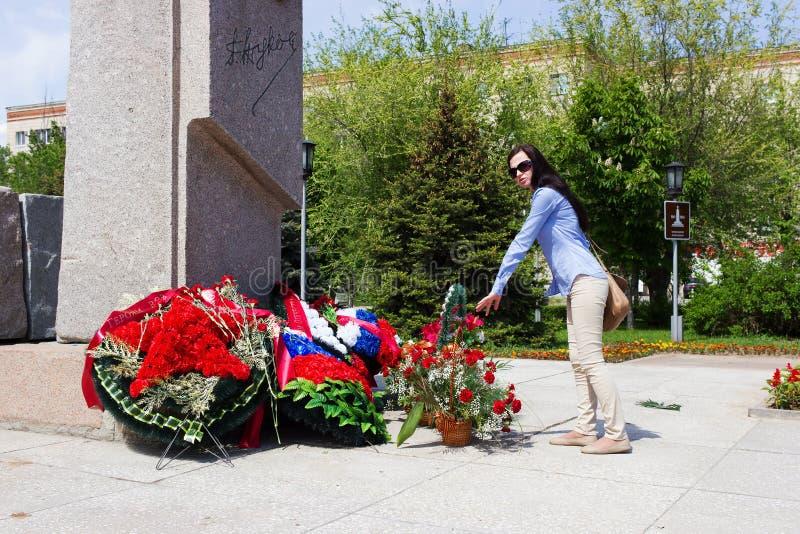 A menina antes de um monumento com flores fotos de stock royalty free