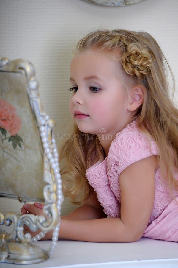 A menina ao lado de um espelho imagens de stock royalty free