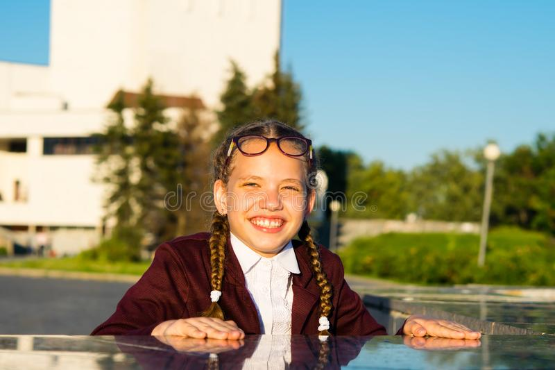 A menina após lições da escola joga no parque e esconde de seu amigo fotografia de stock royalty free
