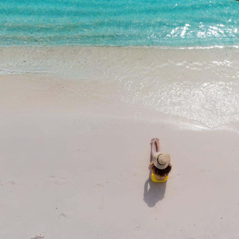 A menina apenas no litoral e aprecia o sol Jovem mulher em um chapéu de palha e em um roupa de banho amarelo imagens de stock royalty free