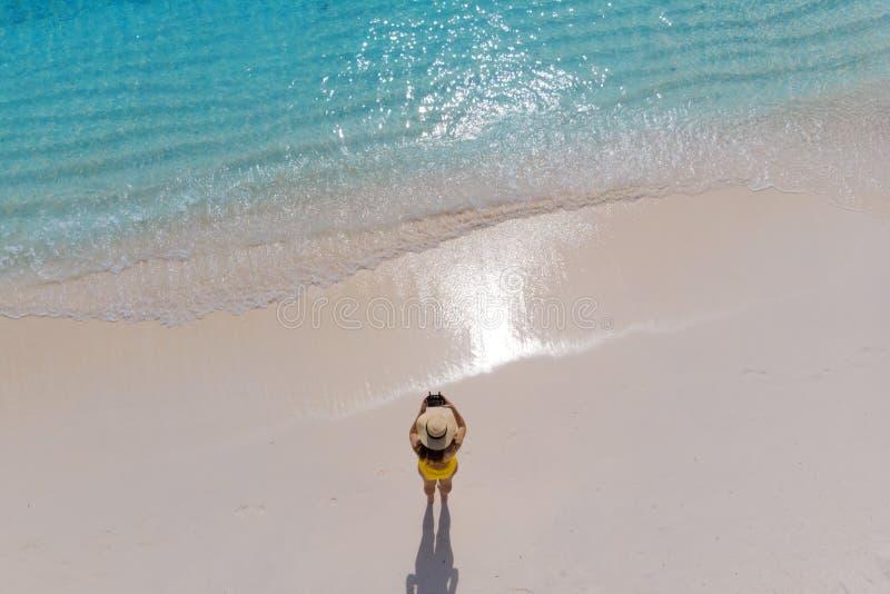 A menina apenas no litoral e aprecia o sol Jovem mulher em um chapéu de palha e em um roupa de banho amarelo fotografia de stock