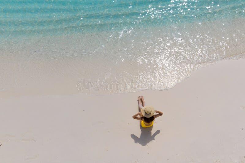 A menina apenas no litoral e aprecia o sol Jovem mulher em um chapéu de palha e em um roupa de banho amarelo imagem de stock