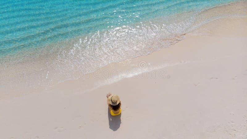 A menina apenas no litoral e aprecia o sol Jovem mulher em um chapéu de palha e em um roupa de banho amarelo imagem de stock royalty free