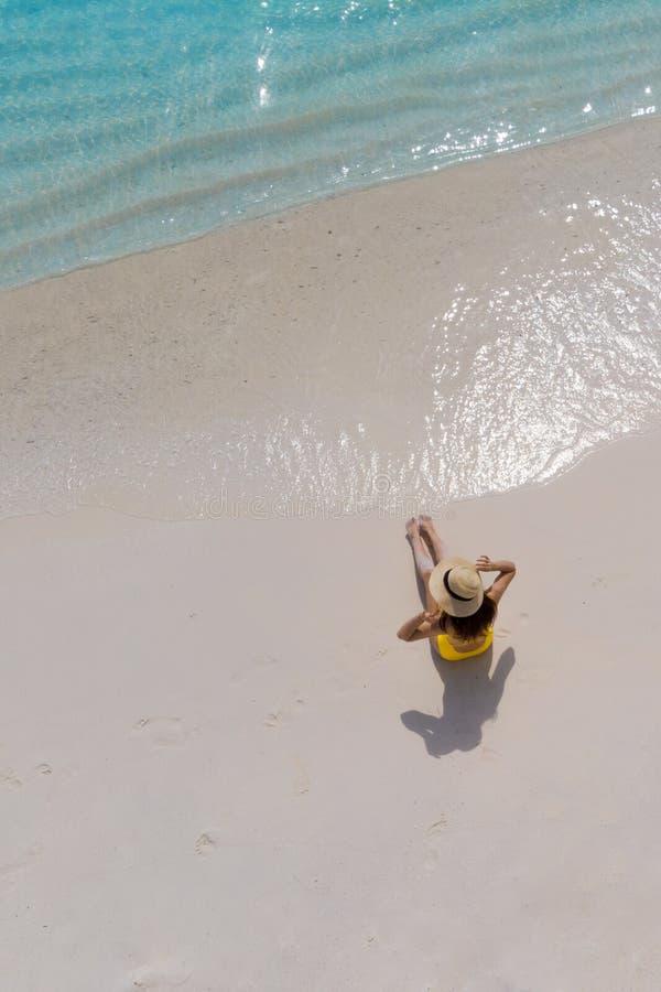 A menina apenas no litoral e aprecia o sol Jovem mulher em um chapéu de palha e em um roupa de banho amarelo fotos de stock royalty free