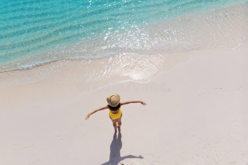 A menina apenas no litoral e aprecia o sol Jovem mulher em um chapéu de palha e em um roupa de banho amarelo foto de stock royalty free