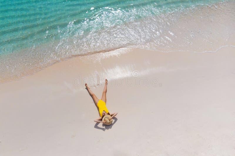 A menina apenas no litoral e aprecia o sol Jovem mulher em um chapéu de palha e em um roupa de banho amarelo que encontram-se na  fotos de stock royalty free