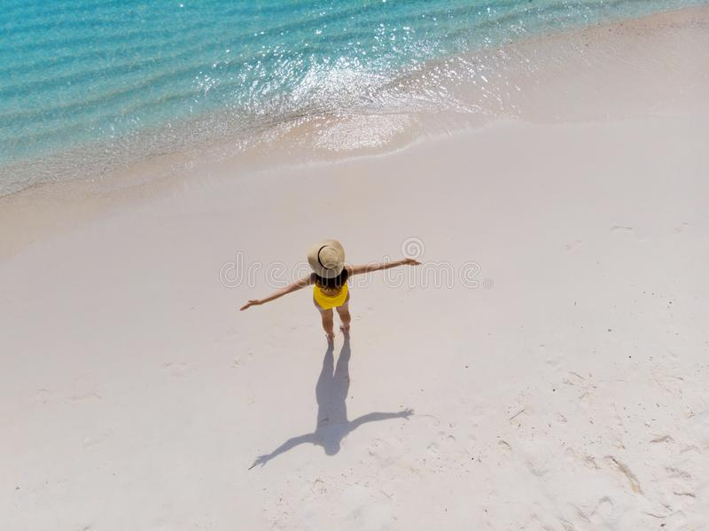 A menina apenas no litoral e aprecia o sol Jovem mulher em um chapéu de palha e suportes amarelos do roupa de banho com os braços imagens de stock royalty free