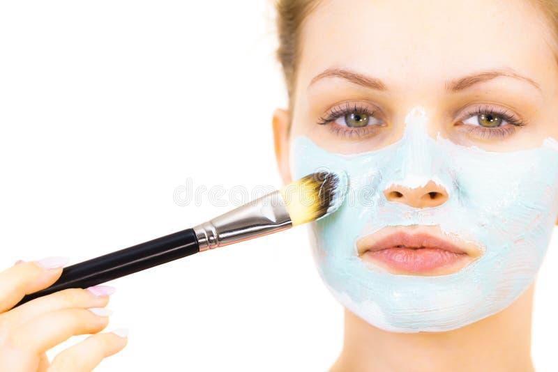 A menina aplica a m?scara verde da lama para enfrentar foto de stock royalty free