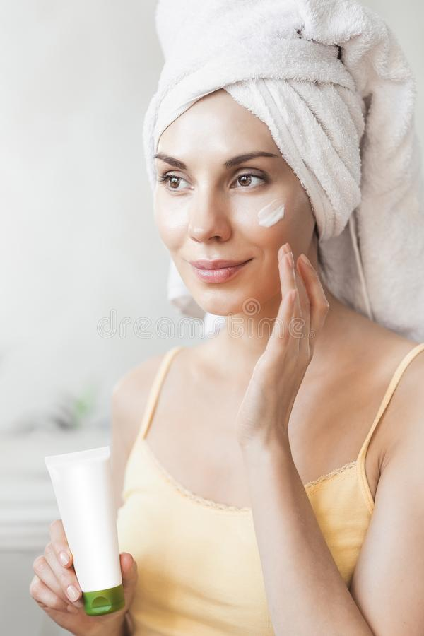 A menina aplica o creme de cara Conceito dos cuidados com a pele e da beleza Jovem mulher que aplica o creme hidratante em sua ca imagem de stock