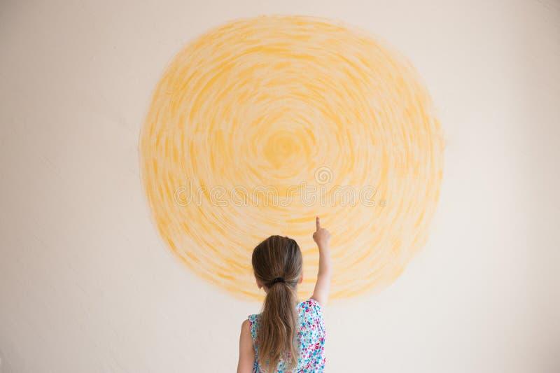 A menina aponta seu dedo no sol amarelo pintado na parede fotos de stock royalty free