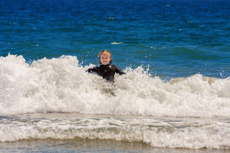 A menina aprecia jogar em ondas de oceano fotos de stock royalty free