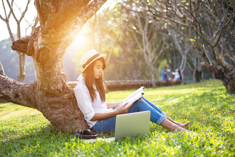 A menina aprecia ler um livro sob a árvore foto de stock