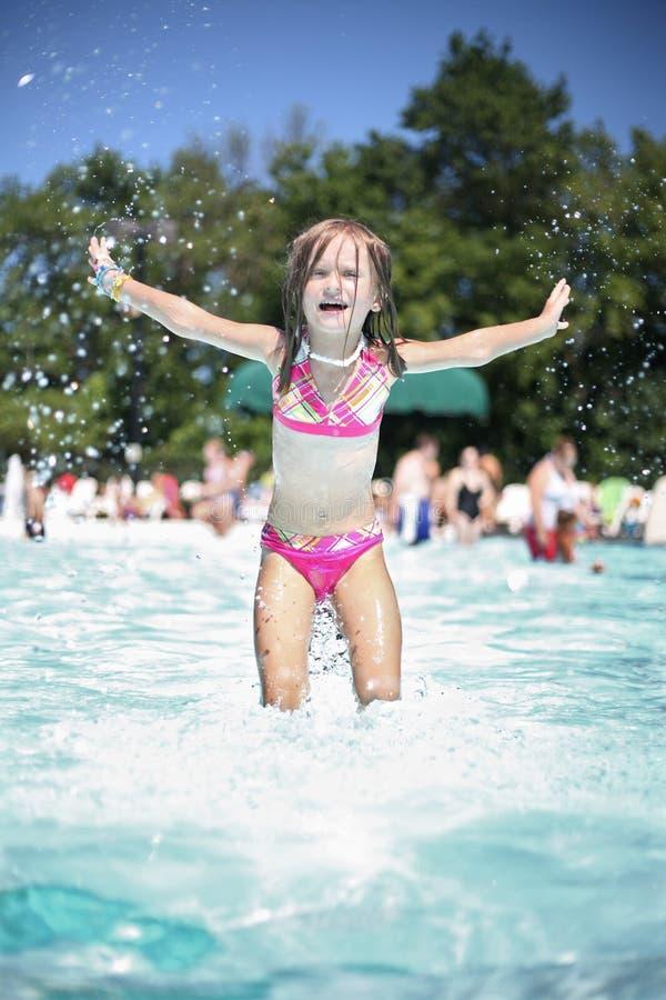 A menina aprecia o dia de verão na piscina. imagem de stock