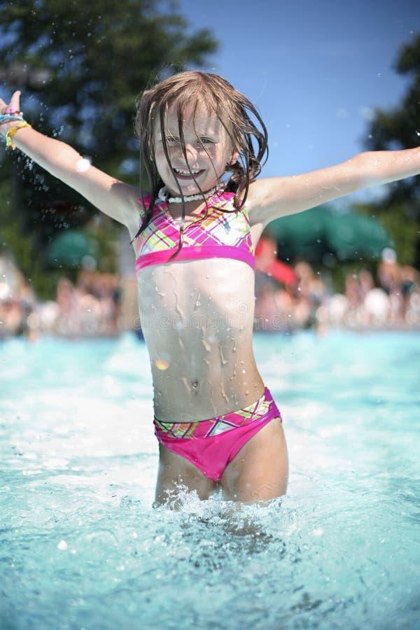 A menina aprecia o dia de verão na piscina. imagens de stock