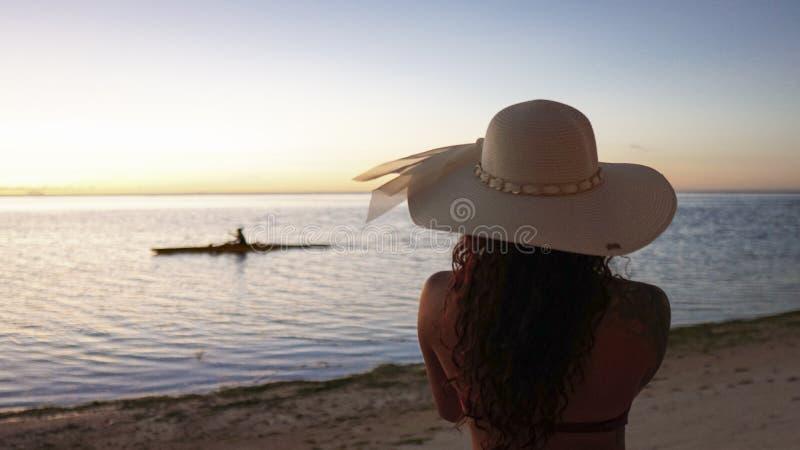 A menina aprecia a opinião o Paddler da praia fotos de stock royalty free