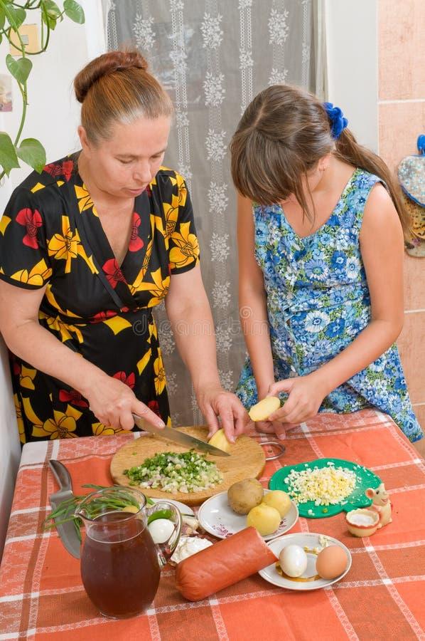 A menina aprende cozinhar um jantar. imagem de stock