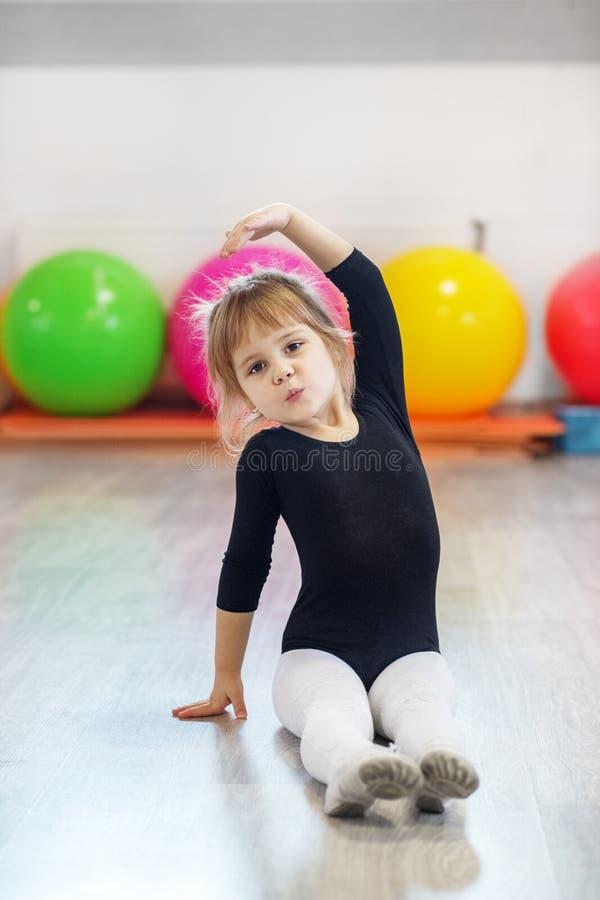 A menina aprende a dança no gym O conceito dos esportes, da educação, dos passatempos, do treinamento e da dança imagens de stock royalty free