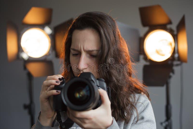 A menina aprende fazer fotos na câmara digital imagem de stock royalty free