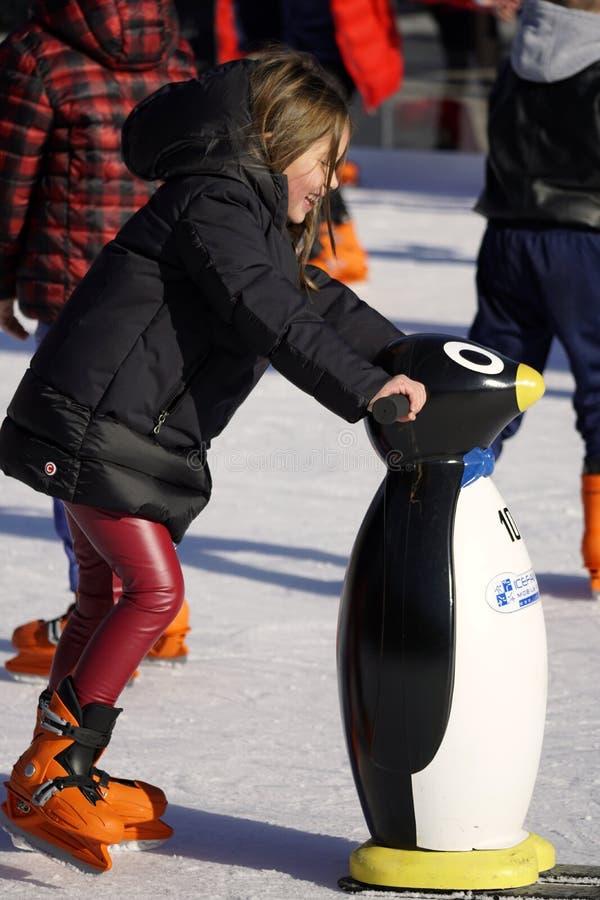 A menina aprende a patinar no gelo com um manequim fotos de stock royalty free