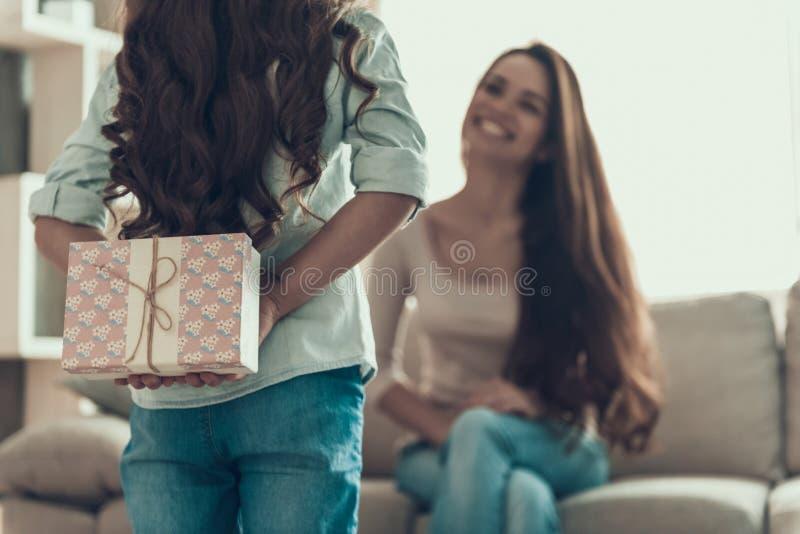Menina aproximadamente para dar o presente à jovem mulher imagem de stock