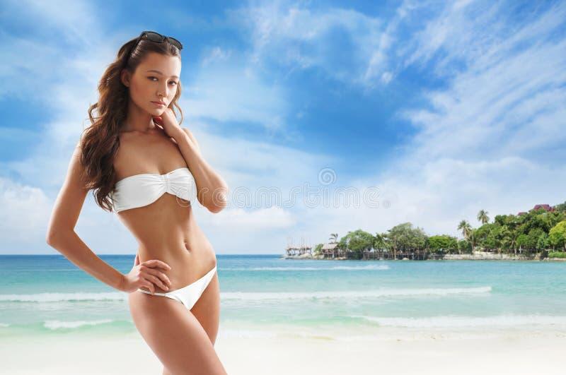 Menina apta e desportiva em um roupa de banho que relaxa na praia imagens de stock royalty free