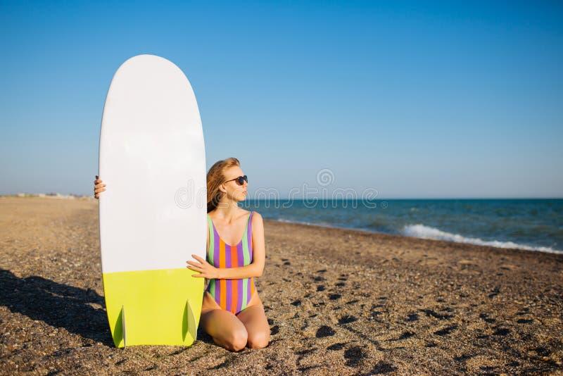 Menina apta nova do surfista na praia com uma placa de ressaca fotos de stock royalty free
