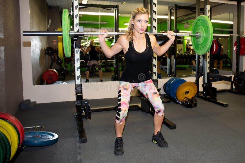Menina apta nova no gym que faz exercícios da ocupa com peso fotos de stock