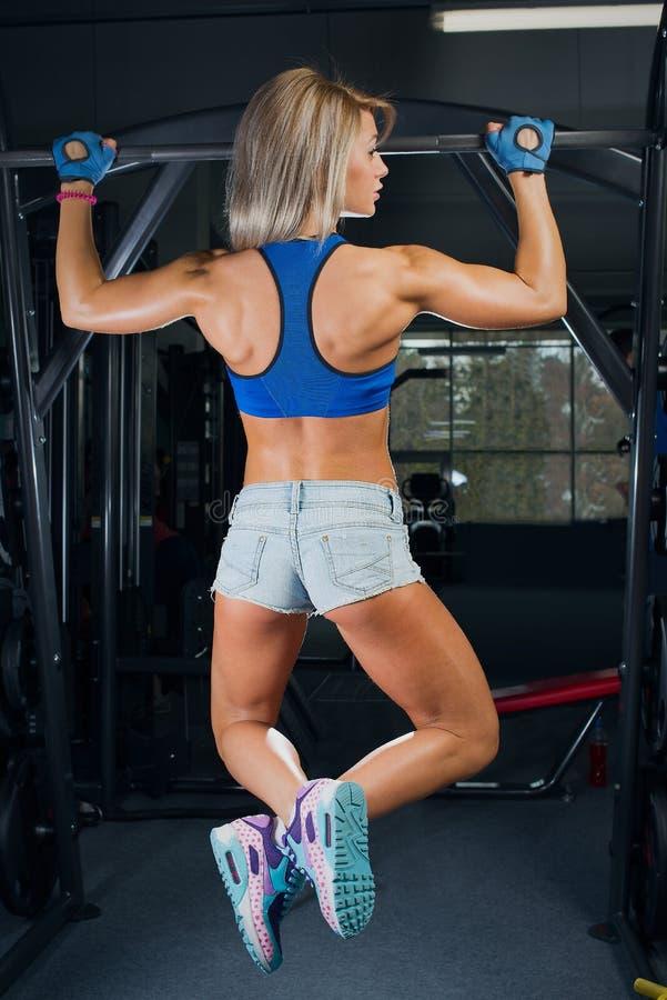Menina apta que alcança na barra no short de uma sarja de Nimes e na parte superior azul no gym imagens de stock