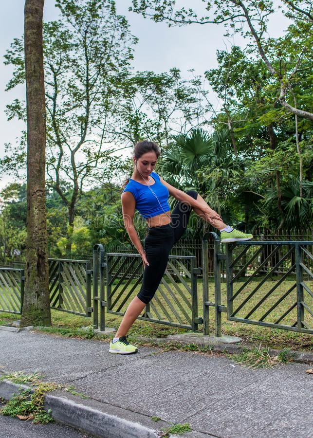 Menina apta que faz esticando o exercício na cerca no parque Atleta fêmea que prepara-se para o exercício da manhã ou que movimen foto de stock
