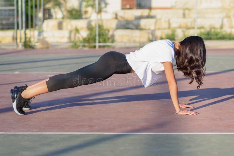 Menina apta que faz o exerc?cio da prancha exterior no dia de ver?o morno do parque imagens de stock royalty free