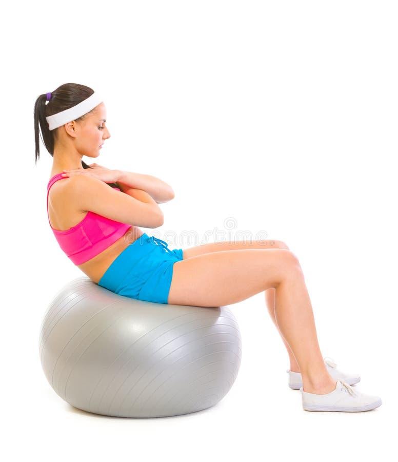 Menina apta que faz a trituração abdominal na esfera da aptidão imagens de stock royalty free