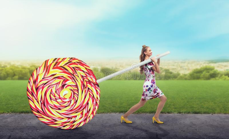 A menina arrasta uns doces coloridos enormes foto de stock royalty free