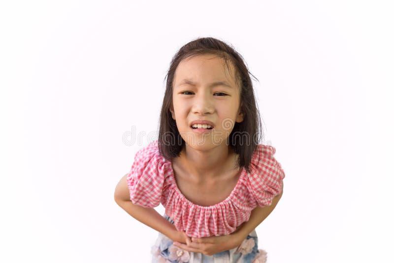 A menina asiática é dor de estômago dolorosa isolada no fundo branco, na criança que têm a intoxicação alimentar, na doença e nos fotografia de stock