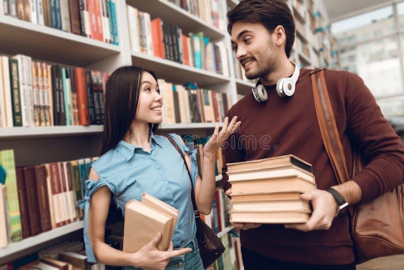Menina asiática étnica e indivíduo branco na biblioteca Os estudantes estão procurando livros fotografia de stock royalty free