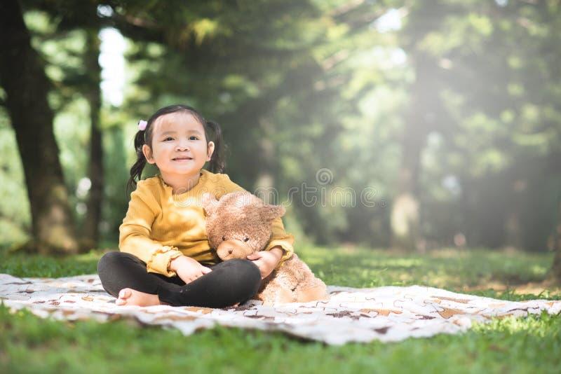 Menina asiática abraçando seu ursinho num parque fotos de stock