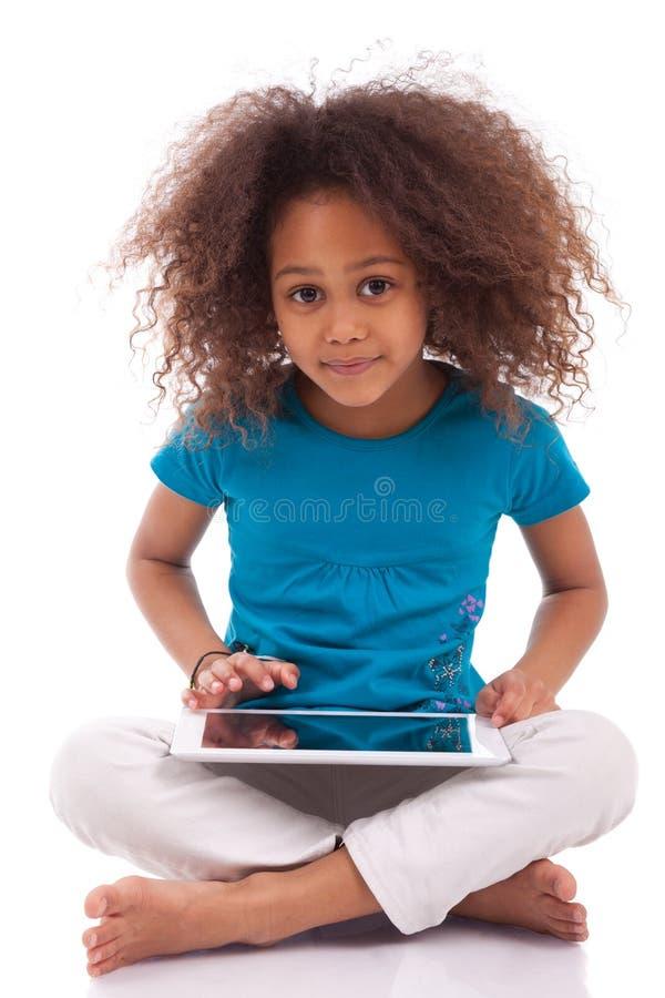 Menina asiática africana pequena que usa um PC da tabuleta